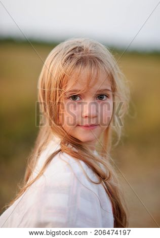 Portrait of the charming girl of 9-10 years. Wind plays with long blonde hair. Serious look of big green eyes. Gentle half-smile.