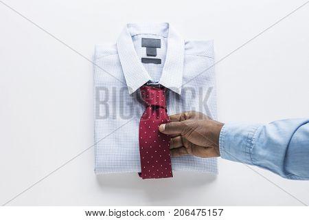 Man hand touching necktie on fold shirt