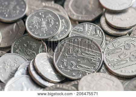 Low denomination British currency. Background image of five pence coins in a pile with selective focus.