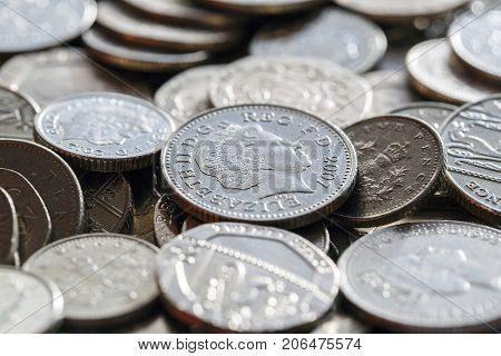 London, UK: January 16, 2016: Low denomination British currency. Background image of five, ten and twenty pence coins in a pile with selective focus.