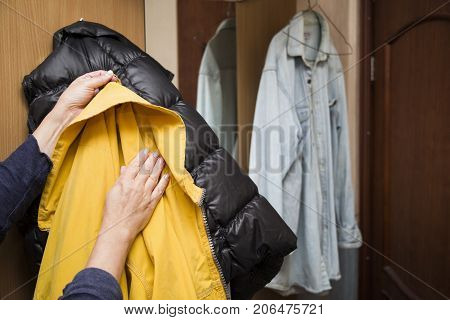 Female hands with yellow raincoat a hallway in the blurred background