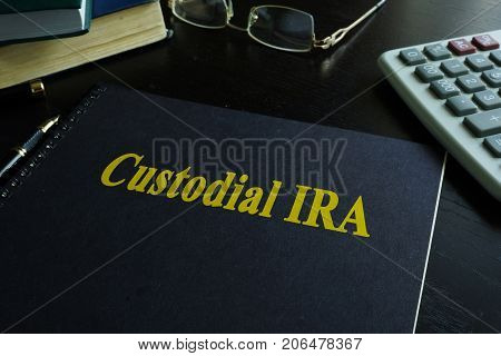 Book with title Custodial IRA on a desk.