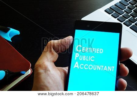 Hand holding phone with sign Certified public accountant (CPA).