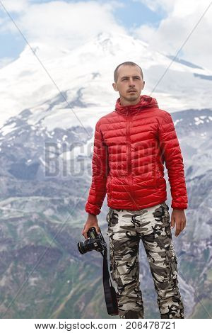 Male photographer with camera in hands stands on a background of mountains Elbrus. Ice the top of mount Elbrus behind men