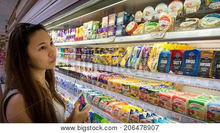 BANGKOK THAILAND - AUGUST 19: An unidentified Thai woman in her 30's shops for packaged cheese and yoghurt in the dairy aisle in Foodland Supermarket on August 18 2017 in Bangkok.