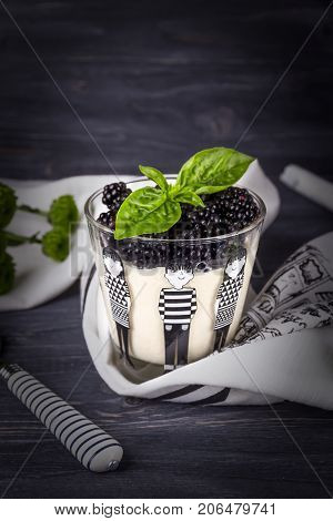 Homemade panna cotta with fresh blackberries and green basil on a dark wooden background