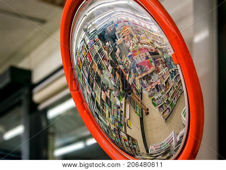 BANGKOK THAILAND - August 27: Convex mirror shows an unidentified customer with an unidentified cashier in a 7-Eleven convenient store on August 27 2017 in Bangkok.