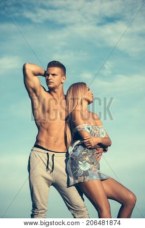 Bodybuilder with muscular torso. Girl with blond hair and bare shoulders. Man and woman posing on blue sky. Couple in love on sunny summer day. Bodybuilding and fitness. Vacation and lifestyle concept