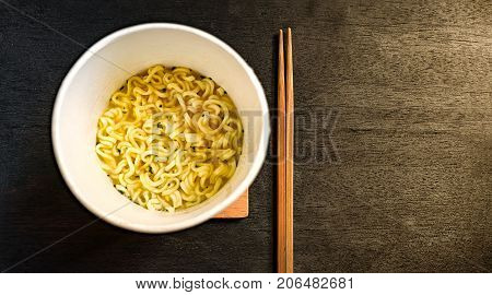 Instant Cup Noodle on Wooden Surface with a Pair of Chopsticks