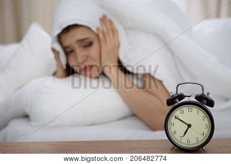 Beautiful sleeping woman lying in bed and trying to wake up with alarm clock. Girl having trouble with getting up early in the morning, Nightmare.