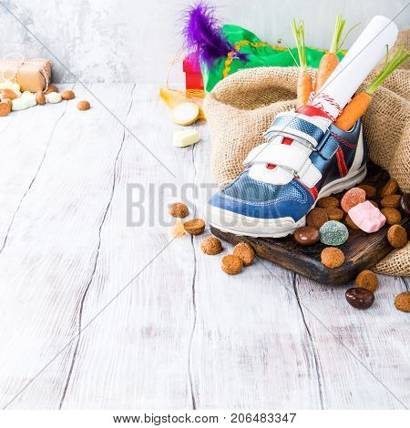 Dutch holiday Sinterklaas composition with childrens shoe with carrots for Santa's horse and sweets with copy space