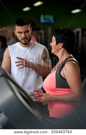 Young male personal trainer talking with female middle aged client in modern gym. Brunette woman working out on treadmill with the assistance of coach. Healthy lifestyle concept. Selective focus