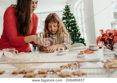 Mother teaching her daughter to make cookies. Woman with her daughter making Christmas cookies using dough mould.