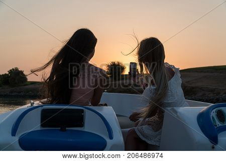 Girls Ride A Boat On The Channels Of The City Of El Gouna And Make Photo On A Mobile Phone