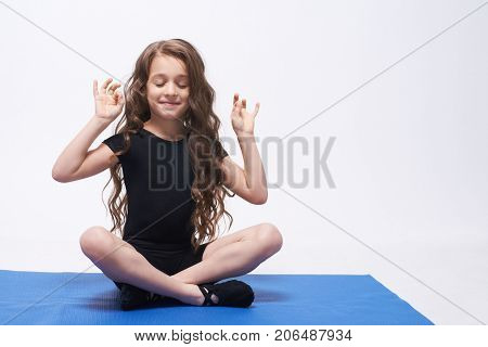 Yoga. Relax. Equilibrium. Lotus position. Curly girl. Brunette.
