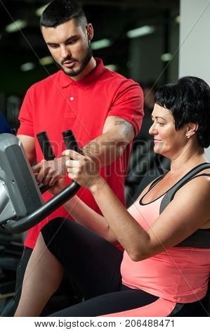 Friendly personal coach with female client in gym. Middle aged brunette woman working out in exercise machine. Healthy lifestyle, fitness and sports concept.