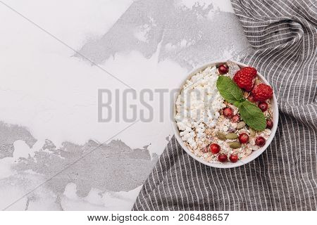 One bowl with cottage cheese with muesli cowberry raspberries and mint on white shabby background. Healthy breakfast concept. Copy space at left
