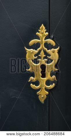 brass keyhole in a dark wooden door