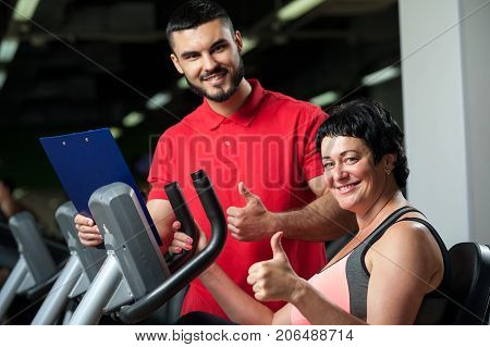 Smiling friendly personal coach with female client in gym. Middle aged brunette woman working out in exercise machine. Healthy lifestyle, fitness and sports concept.