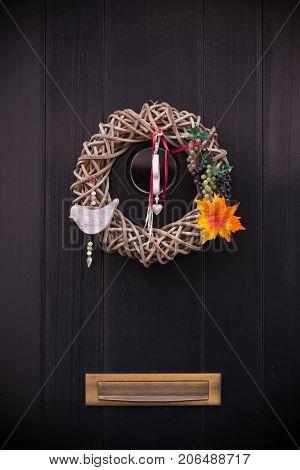 creative door decoration on a dark wooden door with mailbox