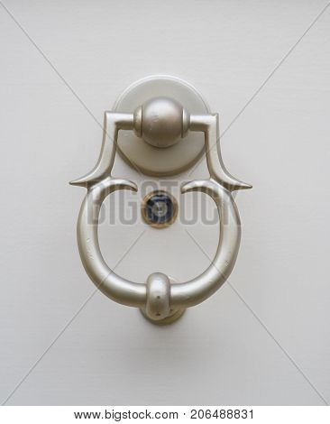 closeup of a metal doorknob with a small peephole under it