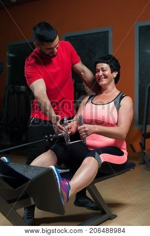 Young fitness coach assisting middle aged woman while she working out on exercising machine. Healthy lifestyle and fitness concept.