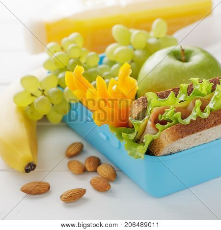 Healthy Snack In Blue Plastic Lunch Box On White Wooden Table.