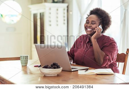 Smiling African woman sitting at her kitchen table at home talking on a cellphone and using a laptop while operating her home based business