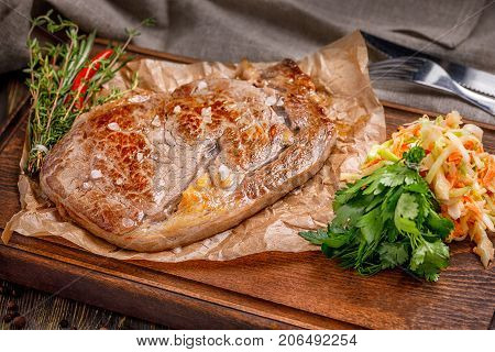 Delicious fresh fried steak on a wooden board for serving with seasonings and herbs, a large piece of fried meat. Macro.