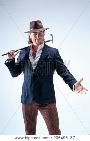 The mature man in a suit and hat holding cane. Isolated on a gray studio background.