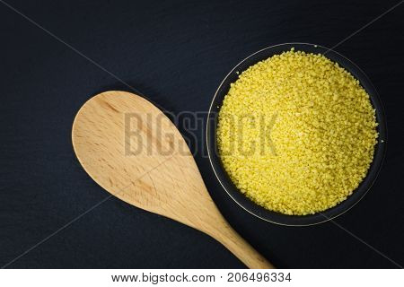 Food concept Raw organic couscous in bowl on slate stone plate with copy space