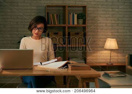 Pretty college student working with books and textbooks at her table