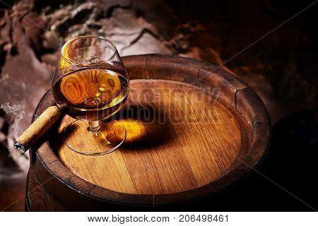 Cognac And Cigar On Old Oak Barrel.