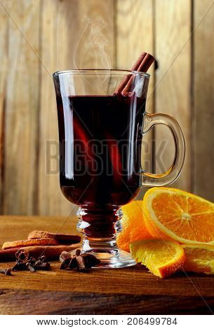 Hot mulled wine glass with spices canmon sticks, star anise, dried lemon on a wooden table.Vertical shot.Cutted orange.Selective focus.Wooden background