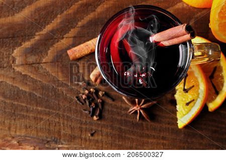 Hot mulled wine glasses with spices canmon sticks, star anise, dried lemon on a wooden table.Vertical shot.Cutted orange.Selective focus.Top view.Focus on glass