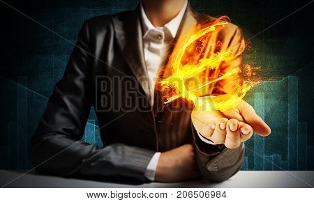 Close-up of businessman in suit presenting flaming euro sign in his hand with dark background.