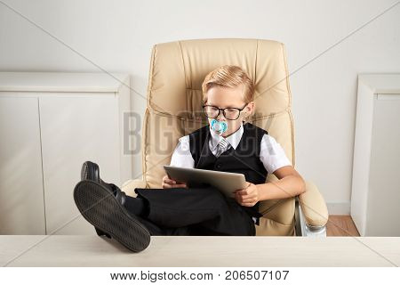 Little businessman with pacifier working on digital tablet at his table