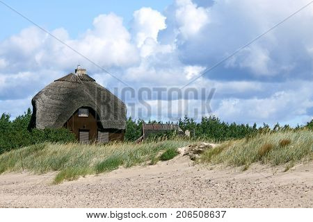 Beach house with thatched roof standing in the sand dunes