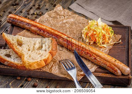 Long sausage grilled. with vegetable salad. Fast food in the restaurant. Delicious fried sausages. Grilled sausages from fresh meat.
