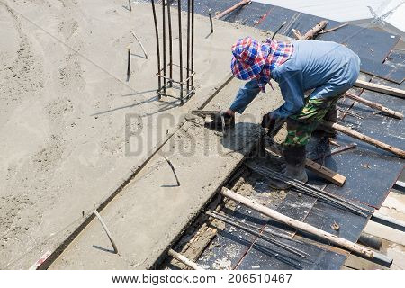 Construction worker spreading poured concrete floors of buildings