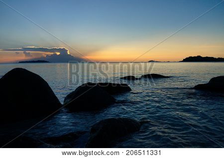 Dark Black Silhouette Rocks In The Ocean At The Coast Of Belitung Island Underneath Blue Sunset Sky,