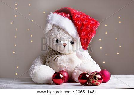 white teddy bear. white teddy bear with Christmas red balls. Cute toy bear with christmas balls and santa hat