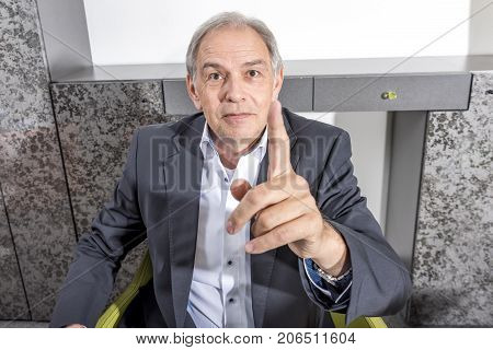Older man in a suit threatens his finger