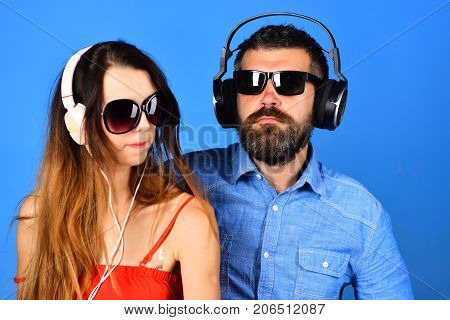 Man with beard and girl sing on blue background. Couple in love wears headphones and sunglasses. Music fans with serious faces enjoy music copy space. Party and music concept.