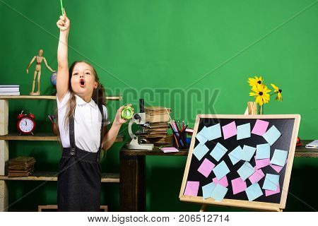 Schoolgirl With Enthusiastic Face In Classroom. Back To School