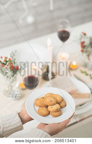 Woman bringing cookies as dessert for the dinner