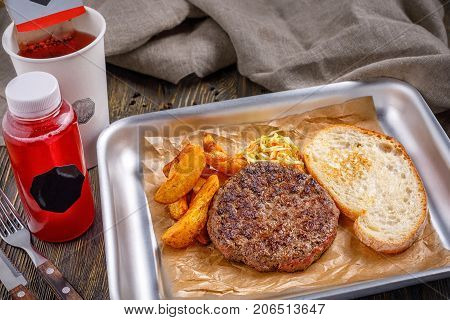 Fast food in a restaurant. A well-fried delicious cutlet with golden crispy french fries and toasted crispy toast. Menu.