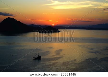 Orange Sunrise View From Padar Island Part Of Komodo National Park With Little Silhouette Boat In Th