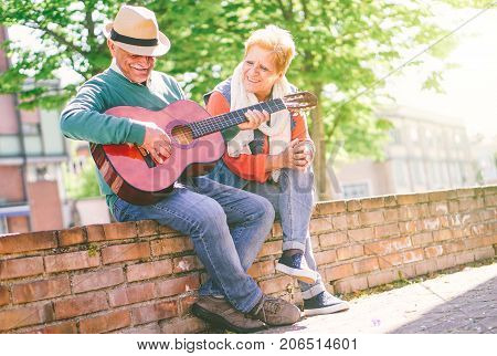 Happy senior couple playing a guitar while sitting outside on a wall on a sunny day - Concept of active elderly having fun with guitar - Enjoying lifestyle during retirement