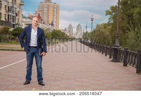 Handsome Bald businessman, realtor in jacket staying on sidewalg over houses background